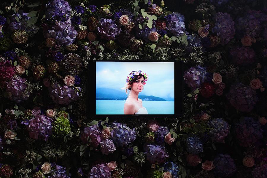 Fleuriste mariage Lyon Atelier Charlotte mur de fleurs violette avec un écran